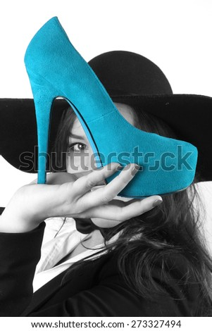 modern young brunette girl with beautiful eyes holding blues female shoes with a high heel and a black hat retro looks - stock photo