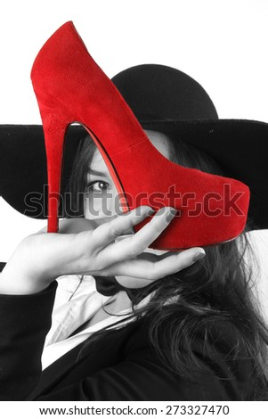 modern young brunette girl with beautiful eyes holding red female shoes with a high heel and a black hat retro looks - stock photo