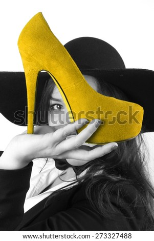 modern young brunette girl with beautiful eyes holding yellow female shoes with a high heel and a black hat retro looks - stock photo
