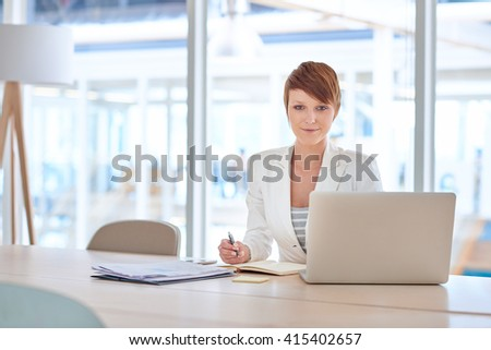 Modern young businesswoman at her desk in a bright office