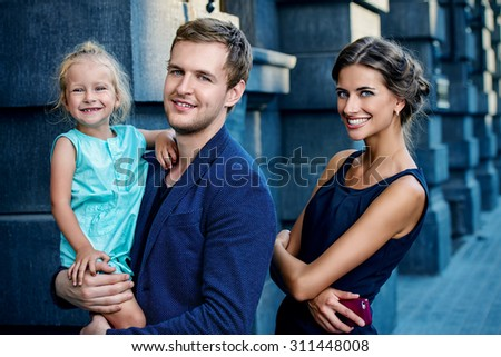 Modern young family walking in the city. Fashion shot. - stock photo