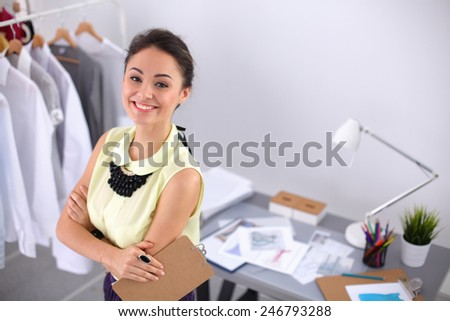 Modern young fashion designer working at studio.isolated - stock photo
