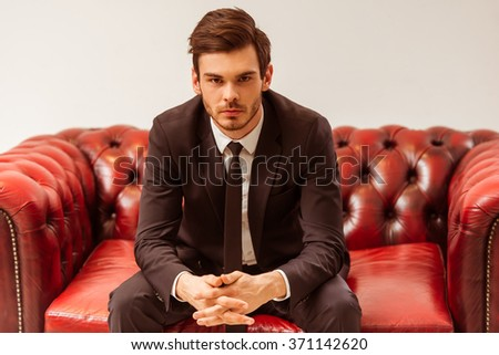Modern young handsome businessman dressed in classical suit posing while sitting on a sofa in the suit shop - stock photo