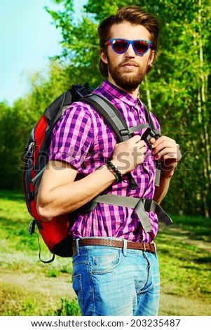 Modern young man hiking in the forest. Active lifestyle, tourism.