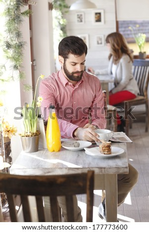 Modern young man sitting at table in coffee shop.  - stock photo
