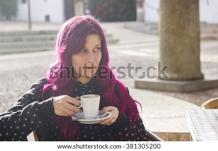 Modern young woman drinking coffee on the terrace of a cafe  - stock photo
