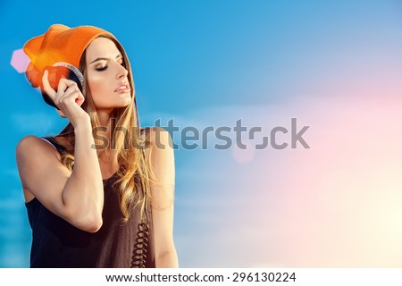 Modern young woman listening to music on headphones outdoor. Trendy teenager girt over blue sky background. Youth style.  - stock photo