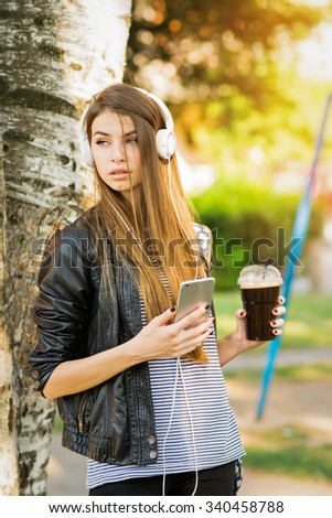 Modern young woman with headphones, smartphone and takeaway coffee in park in autumn. Teenage girl listening music and relaxing outdoors in spring. Vertical, medium retouched, vibrant colors.