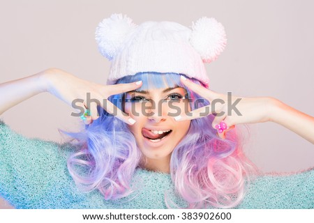 Modern young woman with pastel blue and pink hair, wearing pastel green sweater and white beanie hat with pom poms posing, making funny facial expression. Retouched, studio portrait.