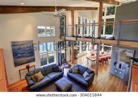 Modernized living room of amazing home with fireplace, and leather sofas. - stock photo