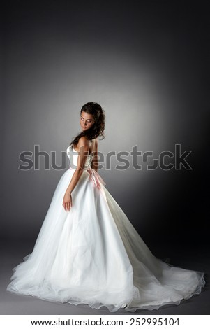 Modest bride posing in elegant dress with plume - stock photo