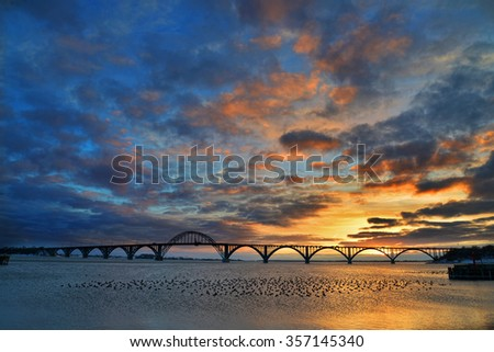 Moen Bridge, Denmark, at sunset. A flock of tufted ducks resting in the foreground