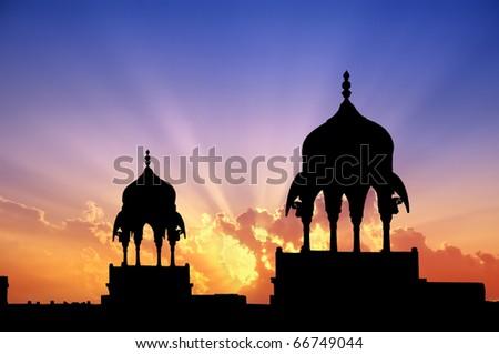 Mogul style pavilions silhouettes at sunset of a Maharajah palace in Bikaner, Rajasthan, India. - stock photo