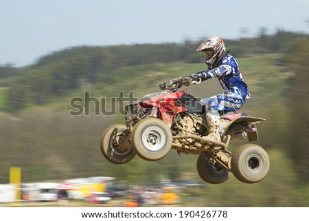 """MOHELNICE,  CZECH REPUBLIC - APRIL 19: Racer in blue  is jumping a quad motorbike in the """"International Championship of the Czech Republic 2014"""" on April 19, 2014  in MOHELNICE, Czech Republic.  - stock photo"""