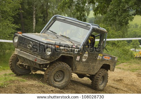 "MOHELNICE, CZECH REPUBLIC - JUNE 10. Unidentified racer at blue off-road car on a steep slope in the ""SHOCK CUP Trial 2012"" on June 10, 2012 in the town of Mohelnice, Czech Republic."