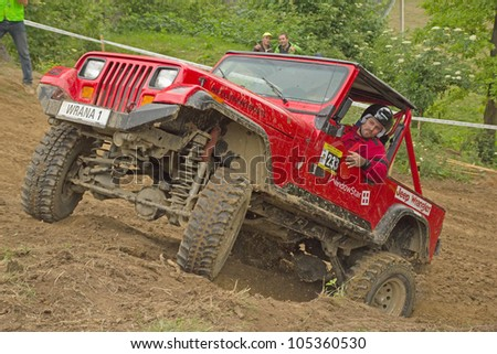 "MOHELNICE, CZECH REPUBLIC - JUNE 10. Unidentified racer at red off-road car leaves steep slope in the ""SHOCK CUP Trial 2012"" on June 10, 2012 in the town of Mohelnice, Czech Republic. - stock photo"