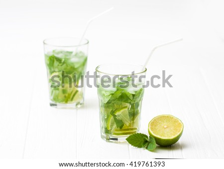 Mohito mojito drink with ice mint and lime on wooden white table. A glass with a refreshing drink