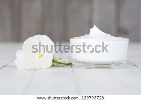moisturizer cream with field roses on white wooden - stock photo