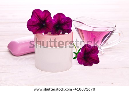 Moisturizing cream with flowers on wooden background - stock photo
