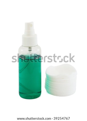 Moisturizing lotion in the plastic bottle with sprayer and a pile of cotton sponges isolated on white - stock photo