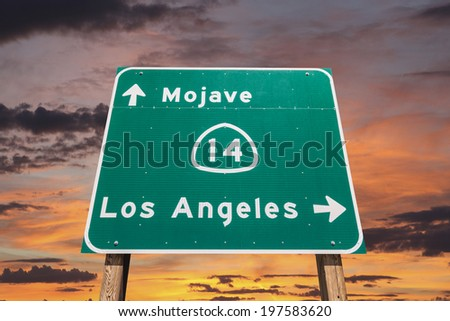 Mojave desert freeway sign towards Los Angeles with sunset sly. - stock photo