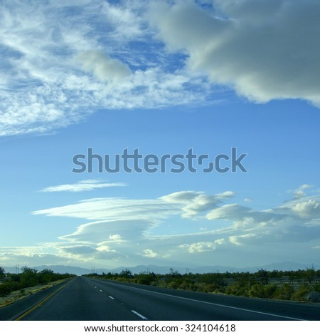 Mojave desert south edge cut by Interstate-10 near city of Desert Centre, California; backlit shot - stock photo