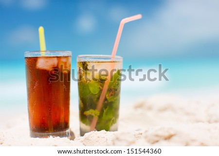 Mojito and Cuba Libre on a tropical beach - stock photo