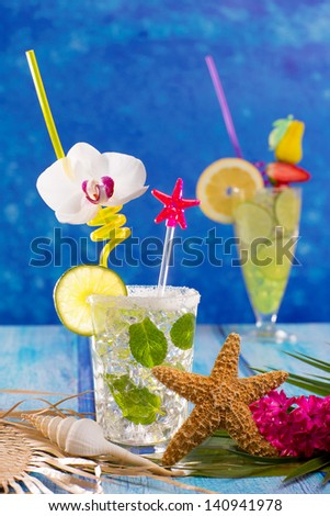 Mojito and lemon lime Cocktails in tropical Caribbean blue wood with starfish flowers and seashells - stock photo