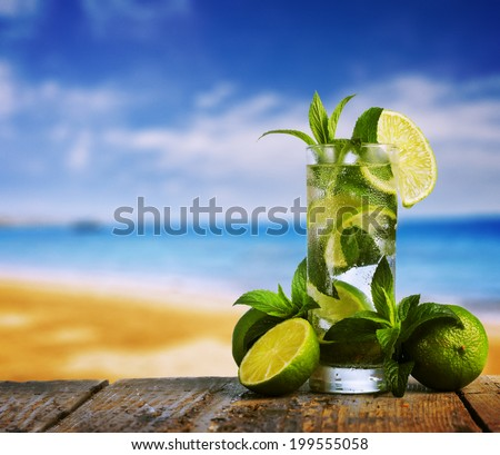Mojito cocktail and beach in the background - stock photo