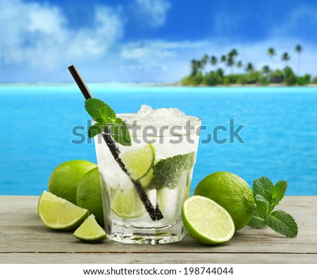 mojito cocktail and fresh ingredients in a tropical landscape - stock photo