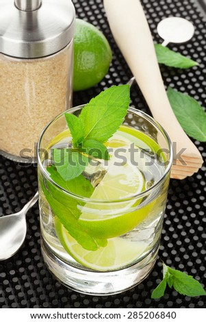 Mojito cocktail and ingredients over black rubber mat - stock photo