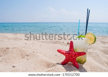 Mojito cocktail and red starfish on the sandy beach with horizon over sea in the background - stock photo