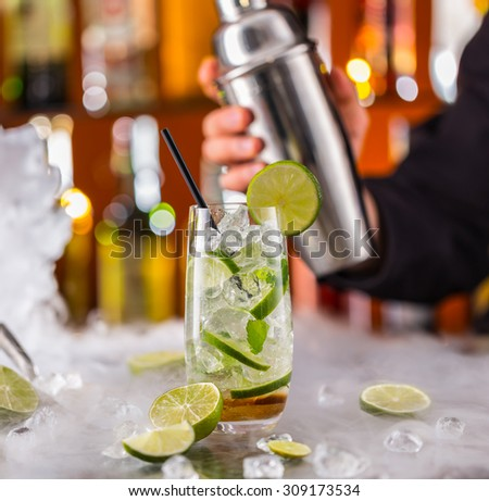 Mojito cocktail drink on bar counter with barman holding shaker on background - stock photo