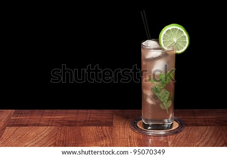 mojito cocktail garnished with fresh mint on a bar top isolated on a black background - stock photo