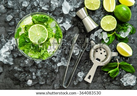 Mojito cocktail ingredients lime, green mint leaves, ice. Drink making accessories - stock photo