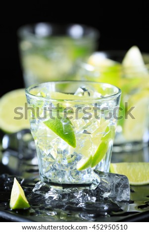 Mojito cocktail on a dark background with lime and ice. Fresh summer cocktail. Vertical