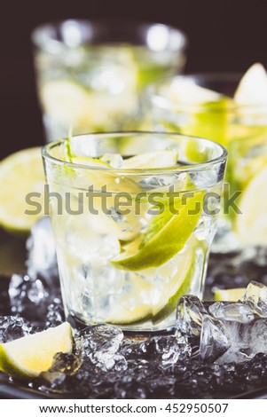 Mojito cocktail on a dark background with lime and ice. Fresh summer cocktail. Vertical. Old-fashioned tone
