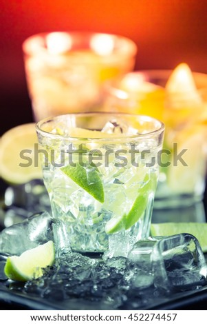 Mojito cocktail on a dark background with lime and ice. Fresh summer cocktail. Vertical. Toned