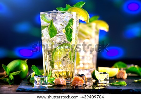 Mojito cocktail on a table in summer bar, Alcohol cocktails with Rum, lime, mint, ice cubes and brown sugar closeup, Party drink. On black background, selective focus - stock photo