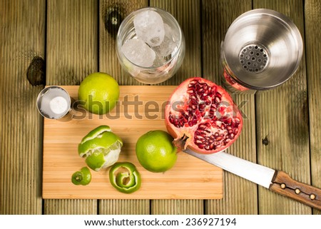 Mojito cocktail preparation: limes, kitchen knife, shaker and a shotglass full of ice - stock photo