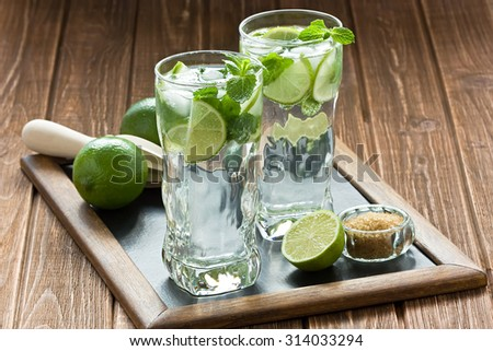 Mojito cocktail refreshing summer drink on rustic wooden table