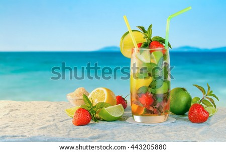 Mojito cocktail. White rum cocktail with fresh ingredients. Cold ice drink on blurred beach background.  - stock photo