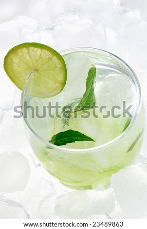 Mojito cocktail with a lime on ice background. - stock photo