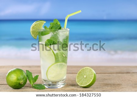 Mojito cocktail with fruits on the beach while on vacation - stock photo