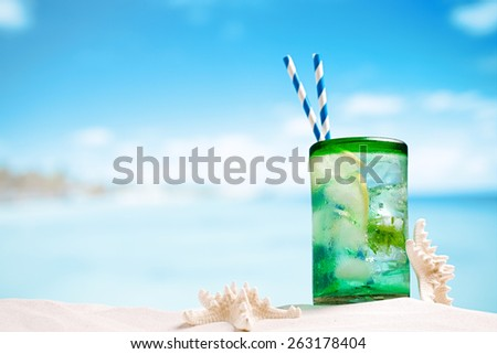 mojito cocktail with ice, rum, lemon and mint in a glass on beach sand and seascape - stock photo