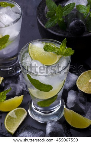 Mojito cocktail with lime and glass on black stone background