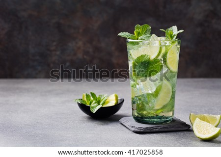 Mojito cocktail with lime and mint in highball glass on a grey stone background Copy space - stock photo