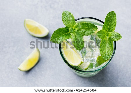 Mojito cocktail with lime and mint in highball glass on a grey stone background Top view Copy space - stock photo
