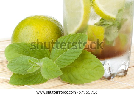Mojito cocktail with lime, leaves of mint and pieces of ice on a white background