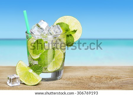Mojito cocktail with lime over tropical beach background